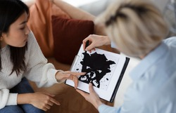 Psychology Test. Psychotherapist Testing Female Patient Showing Inkblot Picture During Therapy Session Sitting In Office. Selective Focus