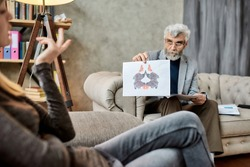 Psychotherapist showing Rorschach inkblot test pictures to young caucasian woman during session in office, selective focus. Psychotherapy concept