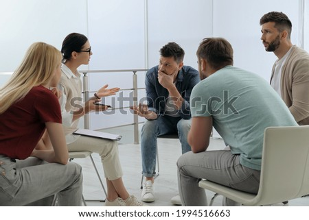 Psychotherapist working with group of drug addicted people at therapy session indoors Stockfoto ©