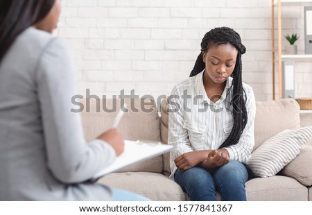 Psychotherapy concept. Upset african american woman sitting on couch at counselor's office