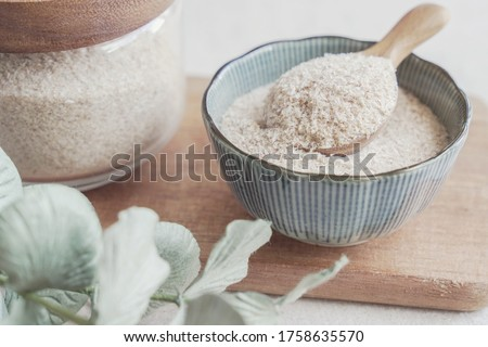 Psyllium husk in wooden spoon and bowl on wooden plate, superfood fiber prebiotic food for gut health Stock photo ©