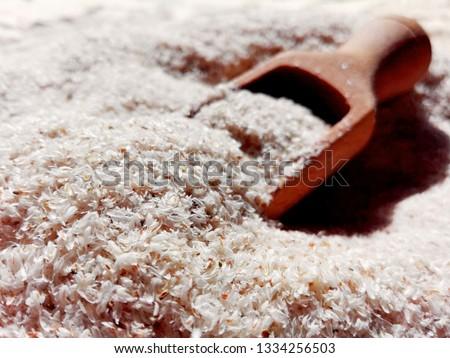 Psyllium isabgol husks heap organic with wooden spoon. Psyllium husk or isabgol soluble fiber derived from seeds of Plantago ovata, usually mixed with water. Psyllium seeds husk organic plantago plant