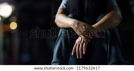 PTSD Mental health concept. Post Traumatic Stress Disorder. The depressed woman sitting alone on the floor in the dark room background. Film look.