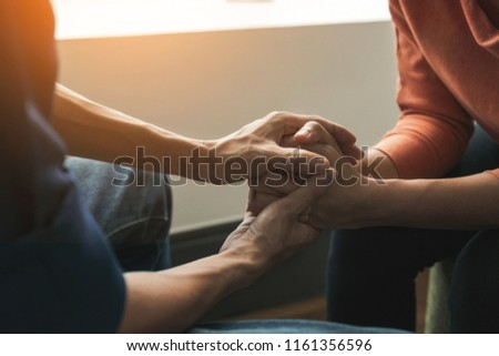 PTSD Mental health concept, Psychologist sitting and touch hand young depressed asian woman for encouragement near window with low light environment.Selective focus.