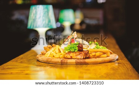 Pub menu snack. Enjoy your meal. Meat snack for group friends. Tasty delicious snacks. Restaurant food. Snack for beer. Wooden board french fries fish sticks burrito and meat steak served with salad.