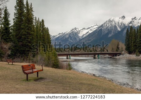 Public bench on the bank of the Bow River with the view of the bridge to downtown Canmore and the Canadian Rocky Mountains in Alberta #1277224183