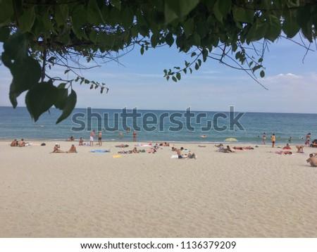 Public city sandy beach people sunbathe on the Black Sea city of Odessa. Ukraine, Odessa, July 2018.
