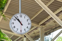 Public clock In a railway station with roof,Black and white classical public hanging clock,The main railway station in Lampang, Thailand.
