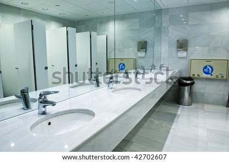 Public empty restroom with washstands, baby changer, and toilets in mirror