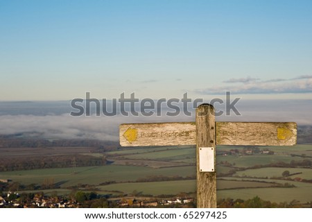 Public footpath signpost pointing in opposite direction, space for copy and text