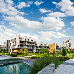 Public green park with modern blocks of flats and blue sky with white clouds