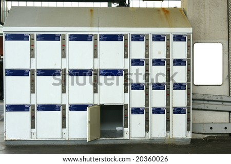 Public luggage lockers at train station with blank billboard next to it