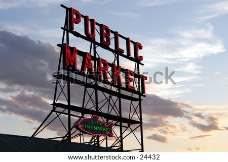 public market sign at sunset with blue skies and fluffy colorful clouds in the background