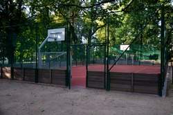 public multifunctional city playground with tartan surface in the park is used to play basketball football floorball goals baskets green safety nets mantineles of wood and game lines of yellow blue