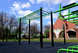 public outdoor exercise and sports park. green stretching and workout equipment. gray rubber safety floor. light brown facade in the background. sports, activity and fitness concept. sportpark