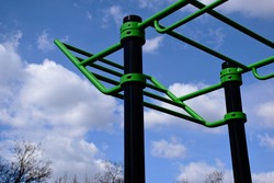 public outdoor physical exercise and sports park. new green and black color stretching and workout equipment. rubber safety floor below. trees in the background. sport, activity and workout concept