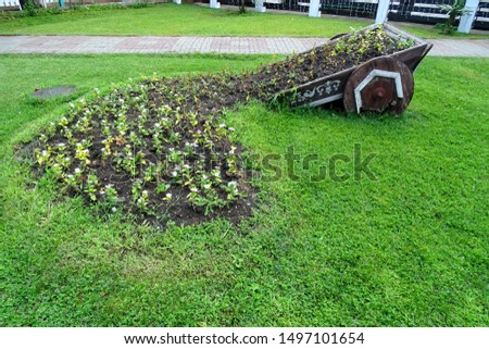 Public park. Flowerbed created in an upturned cart