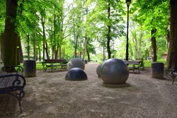 Public park with some benches and trash cans and peculiar spheres and semi spheres made out of metal and stone in the middle of a sand filled area with traces of human feet visible on the surface