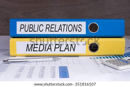 Public Relations and Media Plan - blue and yellow binder on desk in the office