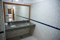 Public restrooms of the school. with modern design, new hand wash, beautiful colored tiles, faucet with mirror and window.