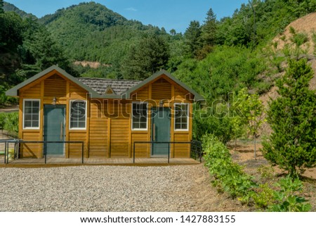 Public restrooms with gravel parking lot in mountain roadside park under blue sky.  #1427883155
