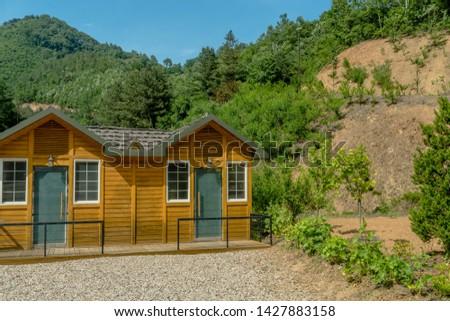 Public restrooms with gravel parking lot in mountain roadside park under blue sky.  #1427883158