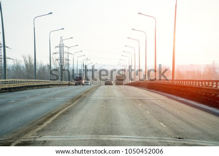 Public road roadway for transport in sunlight. Along the edges of the road, lampposts