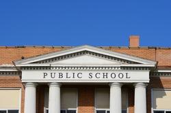 Public school sign on a traditional school entrance