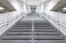 public staircase at station or mall for exit, entrance, emergency. stair inside the metro/subway with cleanly steel handrail. granite staircase.