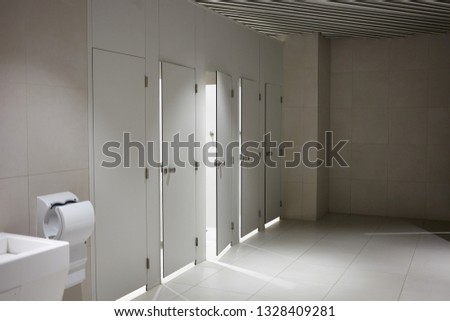 Public toilet cubicles in airport with white doors separated into male and female facilities, accessible to people with disabilities. Sink and hand dryer in empty clean restroom. WC and hygiene