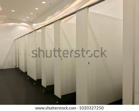 Public toilet design, row of restroom, open doors #1020327250