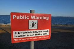 Public Warning sign at low and mid tides the beach is subject to soft and sinking sands. Red and white rectangular sign with icon of person in distress. Blurred beach background.