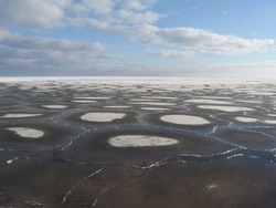 Pucka Bay/Baltic Sea in winter - view with the frozen sea  and round floe in a sunny day. Poland, Pomerania