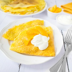 Pudding pancakes with cottage cheese and peaches, topped with sweet cream.