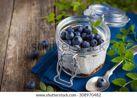 Pudding  with chia seeds, granola and fresh blueberry in glass jar
