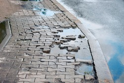 Puddle after rain on damaged paving slabs, dangerous pedestrian walkway. Pit with destroyed gray paving slabs on sidewalk, broken paving stones. Broken slab on pedestrian road