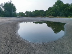 puddle middle of the asphalt road