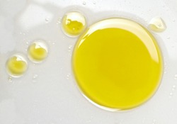 Puddle of natural olive oil in water background, top view