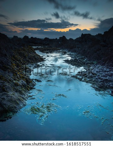 Puddle of water during low tide on rocky beach at twilight in Freshwater West, Pembrokeshire, South Wales,UK.Ethereal, blue hour seascape scene with atmospheric mood.Scenic coastal landscape.