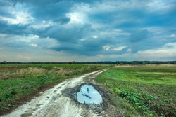 Puddle on the dirt road through the fields and dark rainy clouds