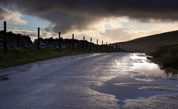 Puddles forming on a country road after heavy rainfall