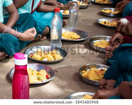 PUDUCHERRY, TAMIL NADU, INDIA - DECEMBER Circa, 2018. Unidentified poor classmates children with uniforms sitting on the floor outdoors, eating with their right hand some rice with masala. Unhealthy