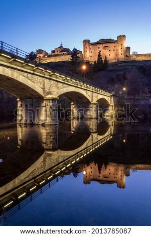 PUEBLA DE SANABRIA, SPAIN - MARCH 20, 2021: Castle and bridge illuminated at night of the medieval village of Puebla de Sanabria reflected on the Tera river, Zamora, Castilla y Leon, Spain Stock fotó ©