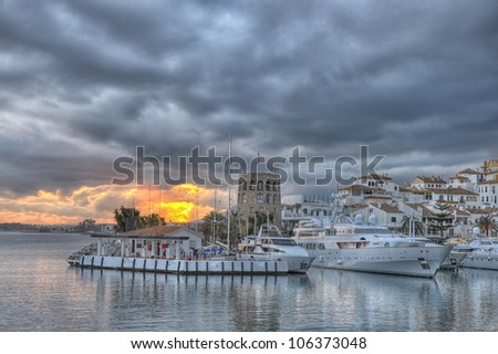 Puerto Banus port surprised at sunset,with a dramatic cloudscape in the background. Puerto Bano is an exclusivist port from Costa del Sol, surrounded by luxury restaurants and stores.