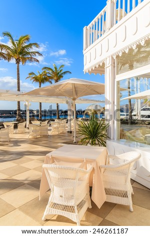 PUERTO CALERO MARINA, LANZAROTE - JAN 17, 2015: Table with chairs on restaurant terrace in Puerto Calero marina built in Caribbean style. Canary Islands are popular holiday destination all year round.