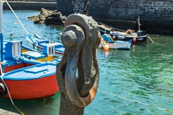 Puerto de la Cruz, Tenerife, Spain - July 10, 2019: Rust anchor in the Old port of town. Small fishing boats of local people. Popular tourist attraction and favorite place for the locals.