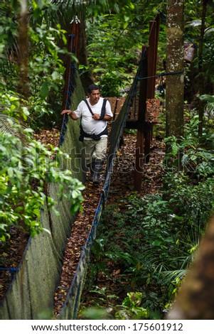 PUERTO MALDONADO, MADRE DE DIOS - PERU, CIRCA 2013: Instant of a unidentified man crossing a canopy walkway in the jungle, CIRCA 2013 in Puerto Maldonado.