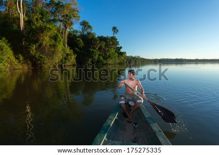 PUERTO MALDONADO MADRE DE DIOS PERU CIRCA 2013 Instant of a unidentified man paddling his boat in the river Circa 2013 in Puerto Maldonado The rivers are the main roads in the Amazon jungle