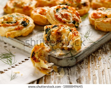 Photo of  Puff Pastry appetizers Pinwheels stuffed with salmon, cheese and spinach on wooden board close-up