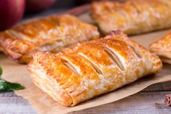 Puff pastry apple pastry turnovers for dessert on a wooden table